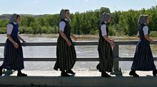 Young Hutterite women from the Standard Colony walk across a bridge over the Red Deer River near Drumheller, Alta., Monday, June 20, 2005. (Jason Scott)