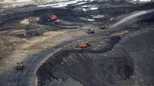 Heavy earth moving machinery move raw tars sands at the Syncrude tar sands mining operations near Fort McMurray, Alberta, in this September 17, 2014 file photo. Crude prices fell another 70 cents Friday to $45.60 and lost more than $3 on the week amid further evidence that global crude stocks are growing rapidly. (TODD KOROL/REUTERS)