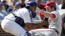 Philadelphia Phillies baserunner Chase Utley slides safely into home plate under the tag of Chicago Cubs catcher Henry Blanco in the fifth inning of their National League baseball game in Chicago, Illinois August 29, 2008. (Reuters)