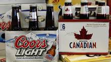 Coors Light and Molson Canadian beers are shown on sale in Denver, Colo., in this 2010 file photo. Molson Coors Brewing Co. said Aug. 6, 2014, its earnings had increased by nearly 10 per cent in the second quarter. (Ed Andrieski/AP)
