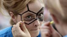 A woman paints the pattern of a soccer ball on her face at the Euro 2012 fan zone in Kharkiv, some 480 km (300 miles) east of Kiev, June 7, 2012. Four Ukrainian cities will host matches for the Euro 2012 soccer championship. (VASILY FEDOSENKO/REUTERS)