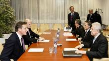 British Prime Minister David Cameron, left, speaks to Italian Prime Minister Mario Monti, right, during a bilateral meeting Thursday before the start of a two-day summit of European leaders at the European Council headquarters in Brussels. (Jock Fistick/Bloomberg/Jock Fistick/Bloomberg)