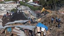 Excavators move earth as rescuers work at the site of a landslide at the main landfill of Addis Ababa on the outskirts of the city on March 12, 2017. (ZACHARIAS ABUBEKER/AFP/Getty Images)