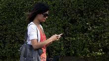 Twenty-five-year-old dancer Natasha Taylor poses for a photo as she walks to work using her newly purchased iPhone after ditching her BlackBerry, in Toronto on June 25, 2012. (Michelle Siu for The Globe and Mail/Michelle Siu for The Globe and Mail)
