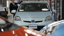 A Toyota Motor Corp. Prius vehicle and other vehicles are displayed at the company's showroom in Tokyo Nov. 14, 2012. Toyota said it will recall around 2.77 million vehicles worldwide, including certain models of the Prius, due to problems with the steering mechanism and the hybrid system water pump, its second multimillion car recall in two months. (YURIKO NAKAO/REUTERS)