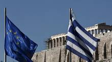 A Greek, right, and European Union flag flutter in front of the Parthenon during the takeover ceremony of the six-month rotation of Greece's EU Presidency at Zappeion Hall, in Athens Jan. 8, 2014. (YORGOS KARAHALIS/REUTERS)
