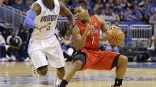 Toronto Raptors guard Kyle Lowry (7) makes a move to get around Orlando Magic's Victor Oladipo (5) during the first half of an NBA game in Orlando, Fla., Sunday, March 30, 2014. (John Raoux/AP)