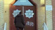 A man looks at new vandalism on the front door of the Outaouais Islamic Centre in Gatineau , Quebec on Thursday, Jan. 5, 2012. (Sean Kilpatrick/Sean Kilpatrick/The Canadian Press)