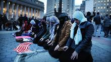 Muslim women pray before a protest in lower Manhattan against the polices of President Donald Trump on February 1, 2017 in New York City. Canadian government has faced widespread calls to suspend the Safe Third Country Agreement.