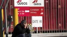 A laid off Aveo employee makes a call in front of the aircraft maintenance company's plant Tuesday, March 20, 2012 in Montreal. (Ryan Remiorz/THE CANADIAN PRESS)