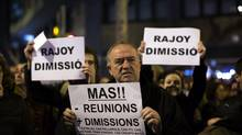 Protesters carry banners reading: 'Rajoy and Mas resignation' during a demonstration against corruption in front of the Popular Party offices in Barcelona, Saturday, Feb. 2, 2013. Spain's prime minister has denied media reports that allege he and members of his governing Popular Party accepted or made under-the-table payments. (Emilio Morenatti/AP)