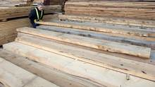 A worker tidies up a wood pile at a lumber yard Tuesday, April 25, 2017 in Montreal. Hundreds of Quebec forestry workers are getting the first sour tastes from the softwood lumber battle with the United States as they prepare for the start of layoffs. (Paul Chiasson/THE CANADIAN PRESS)