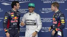 Red Bull Racing driver Daniel Ricciardo of Australia, left, Mercedes driver Lewis Hamilton of Britain, center, and Red Bull Racing driver Sebastian Vettel of Germany, right, chat after the qualifying session of the Chinese Formula One Grand Prix at Shanghai International Circuit in Shanghai, Saturday, April 19, 2014. (Andy Wong/AP Photo)