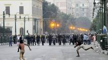 Egyptian protesters hurl stones at riot police in downtown Cairo, in protest against a film ridiculing the Prophet Muhammad. (Anonymous/AP)