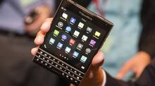 BlackBerry Chief Executive John Chen holds up the unreleased Blackberry Passport device during the company's annual general meeting for shareholders in Waterloo June 19, 2014. (Mark Blinch/REUTERS)