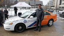 Superintendent Sam Fernandes, Unit Commander of 32 Division, poses beside the Toronto Police Service's RIDE Frankencar. (Constable Tom Rataj)