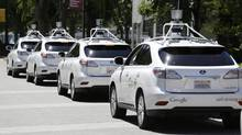 A row of Google's self-driving cars on the roads in Mountain View, Calif., on May 14, 2014. (Eric Risberg/The Associated Press)