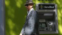 A man walks past in front of an ATM machine at Spain's Bankia in Madrid August 31, 2012. (JUAN MEDINA/REUTERS)
