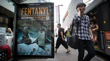 People walk past a bus shelter advertisement warning of the dangers of fentanyl on Granville Street in Vancouver on Aug. 12, 2015. (Darryl Dyck for The Globe and Mail)