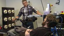 University of Pittsburgh researcher Robert Gaunt preparing Nathan Copeland for research testing to see if brain implants could help the paralyzed man feel sensation in his own hand while using a mind-controlled robotic arm. (Timothy Betler/AP)