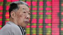 An investor looks at the stock price monitor at a private securities company Wednesday, July 4, 2012 in Shanghai. (Associated Press)