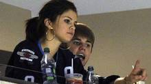 Singer Justin Bieber (R) and his girlfriend Selena Gomez watch the NHL game between the Carolina Hurricanes and Winnipeg Jets in Winnipeg October 22, 2011. REUTERS/Fred Greenslade (Fred Greenslade/Reuters)