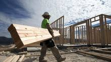 In this Friday, Nov. 16, 2012, photo, construction worker Miguel Fonseca carries lumber as he works on a house frame for a new home in Chula Vista, Calif. (Gregory Bull/AP)