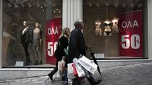 Consumers carry shopping bags outside a shop at a central commercial street of Athens January 16, 2014. Retailers across Europe have been struggling as shoppers' disposable income has been squeezed by subdued wage growth and the government austerity measures. (YORGOS KARAHALIS/REUTERS)