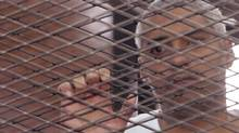 Al Jazeera journalist Mohammed Fahmy stands behind bars at a court in Cairo May 15, 2014. (STRINGER/EGYPT/REUTERS)