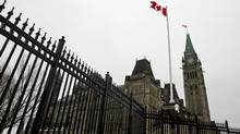 A Canadian flag flies over Parliament Hill on March 21, 2011, after a Commons committee recommended the Harper government be found in contempt. (Sean Kilpatrick/The Canadian Press)