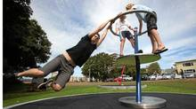 Local artist Tyler Hodgins and his son's Emmett,10, left, and Dexter,12, play around on Tyler's recently unveiled Glass Half Full exhibit, a stainless steel, interactive piece in Holland Point Park, along Dallas Rd. in Victoria, B.C. Sunday, August 21,2011. (Chad Hipolito for The Globe And Mail/Chad Hipolito for The Globe And Mail)