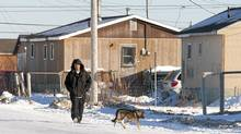 A man walks down the street in Attawapiskat, Ont., Tuesday Nov. 29, 2011. (Adrian Wyld/Adrian Wyld/THE CANADIAN PRESS)
