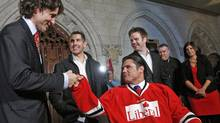 Justin Trudeau bumps fists with Patrick Brazeau after cutting off a lock of his hair in the foyer of the House of Commons on April 2, 2012. The Tory Senator agreed to have his hair cut after losing a charity boxing match to the Liberal MP. (CHRIS WATTIE/Chris Wattie/Reuters)