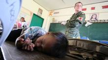 A boy sleeps while Canadian military personnel examine Filipinos during a medical clinic at an evacuation centre conducted by the Canadian Disaster Assistance Response Team, or DART. Aid groups at Roxas City have found very few in need of medical assistance. (Nathan VanderKlippe)
