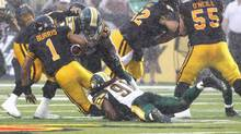 Hamilton Tiger-Cats quarterback Henry Burris, left, is sacked by Edmonton Eskimos' Marcus Howard in the first half of their CFL football game in Guelph, Ont. July 7, 2013. (FRED THORNHILL/REUTERS)