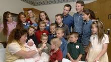 Michelle Duggar, left, is surrounded by her children and husband Jim Bob, third from right, while she holds her newborn daughter, Jennifer Danielle, their 17th child in this August 2007 file photo. (Beth Hall / AP Photo/Beth Hall / AP Photo)