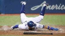 Kevin Pillar slides across home plate to score a run in the fifth inning on Tuesday. (Tom Szczerbowski/Getty Images)
