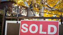 A real estate sold sign hangs in front of a west-end Toronto property in this file photo. (Graeme Roy/THE CANADIAN PRESS)