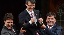 Liberal Leader Justin Trudeau and MP Dominic LeBlanc (right) escort new Liberal MP Arnold Chan in the House of Commons, Monday, Sept. 15, 2014 in Ottawa. (Adrian Wyld/The Canadian Press)