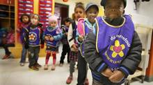 Purple bibs to identify the children of cpe du carrefour, a daycare as they get ready to go outdoors in Montreal, October 17, 2013. ((Christinne Muschi for The Globe and Mail))