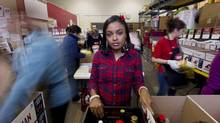 Volunteers pack boxes of food while Cashama Charlery, 22, is photographed inside the North York Harvest Food Bank in Toronto on Monday. Ms. Charlery, a single mother, uses the food bank twice a month, but she also volunteers there two days a week. (PETER POWER/THE GLOBE AND MAIL)