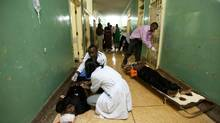 Paramedics treat some of the injured in a hallway at Mulago Hospital in Kampala after separate bomb blasts ripped through two bars packed with soccer fans watching the World Cup final. (STR/Benedicte Desrus/Reuters)
