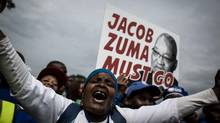 A protester holds a placard reading 'Jacob Zuma must go' during a march against the South African President on Friday in Johannesburg. Thousands demonstrated in South African cities and towns demanding Mr. Zuma's resignation as a second ratings agency downgraded the country's debt to junk status. (JOHN WESSELS/AFP/Getty Images)