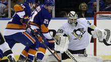 Pittsburgh Penguins goalie Marc-Andre Fleury (29) makes a save as New York Islanders center Josh Bailey (12) and right wing Kyle Okposo (21), of Switzerland, look on in the first period of Game 4 of their first-round NHL Stanley Cup playoffs hockey series at Nassau Coliseum in Uniondale, N.Y., Tuesday, May 7, 2013. (Kathy Willens/AP)