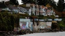 A man walks along the waterfront as a graffiti mural, centre left, commissioned by Lululemon founder Chip Wilson is seen on the seawall at his home amongst graffiti painted by unknown people on the seawalls of other homes in Vancouver, on Tuesday November 5, 2013. (DARRYL DYCK FOR THE GLOBE AND MAIL)