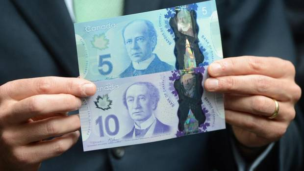 The prime-minister sides of the new $5 and $10 polymer bills, held by Bank of Canada Governor Mark Carney. Former prime minister Wilfrid Laurier features on the $5 bill and first prime minister John A. Macdonald is on the $10. (Sean Kilpatrick/THE CANADIAN PRESS)