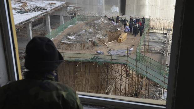A labourer watches as an ancestral tomb is being moved away from a construction site of a residential compound in the city of Taiyuan. The tomb, measuring 10 metres high with a surface 10 metres square, has been left in the middle of the construction site since the building project started about seven months ago. (JON WOO/REUTERS)