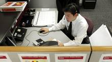 An employee of Vanguard Group Inc. answers calls from investors at the company's headquarters in Malvern, Pennsylvania, U.S. Vanguard is the second-biggest U.S. mutual-fund company. (BRADLEY C BOWER/BLOOMBERG NEWS)