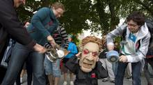 Protesters hit casserole pans in front of a Charest mascot to protest against tuition hikes on Wednesday May 30, 2012 in Quebec City. (Clement Allard/THE CANADIAN PRESS)