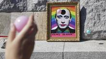 A participant throws a ball towards a picture depicting Russian President Vladimir Putin with make-up during the Prague Pride Parade where several thousand people marched through Prague's city centre in support of gay rights on August 17, 2013. (DAVID W CERNY/REUTERS)